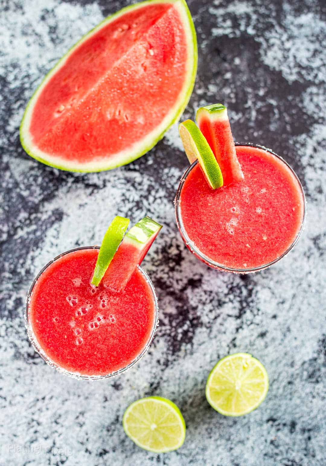 Overhead shot of two Frozen Watermelon Margarita next to a watermelon wedge