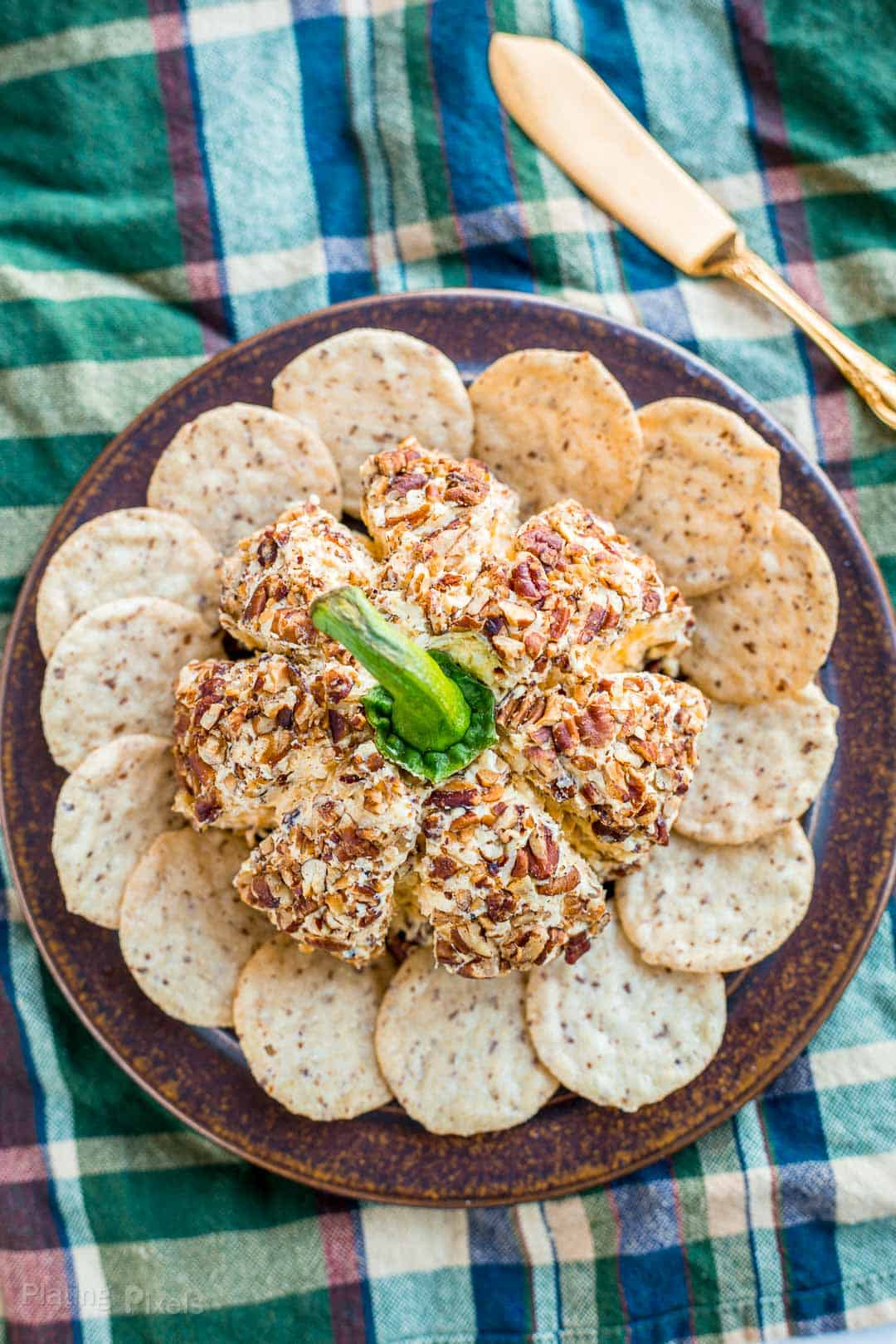 Overhead shot of a Pumpkin Cheese Ball on a plate surrounded by crackers