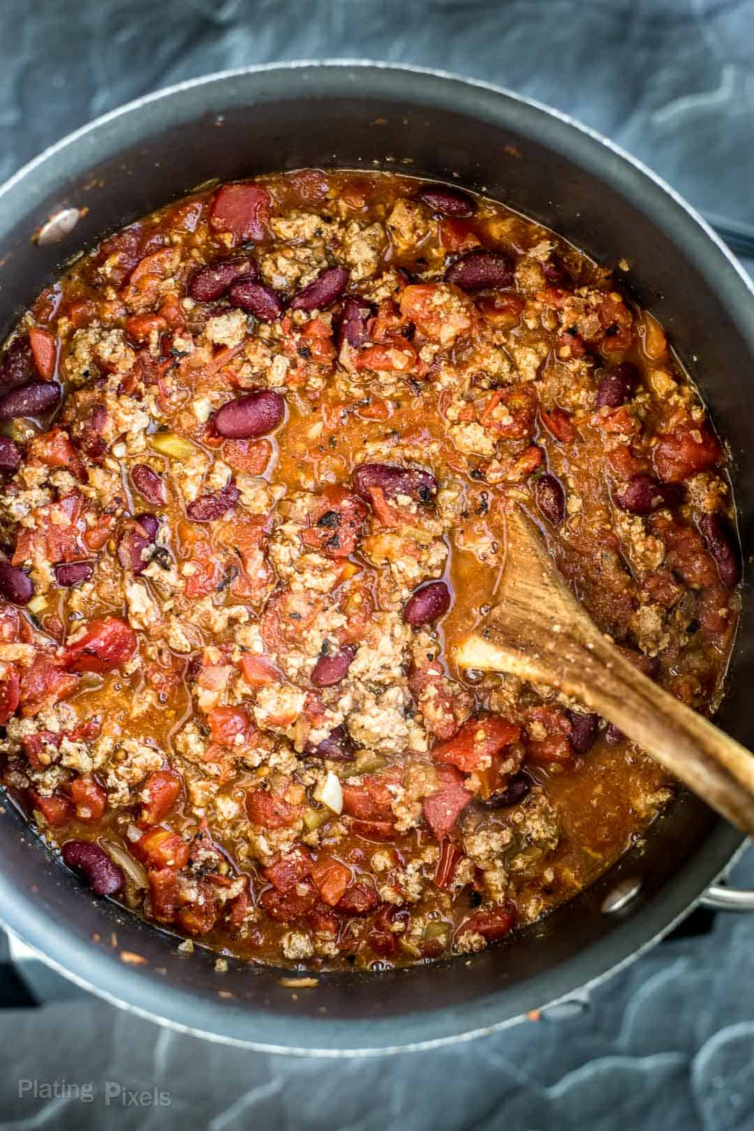 Process shot of adding canned diced tomatoes to turkey chili