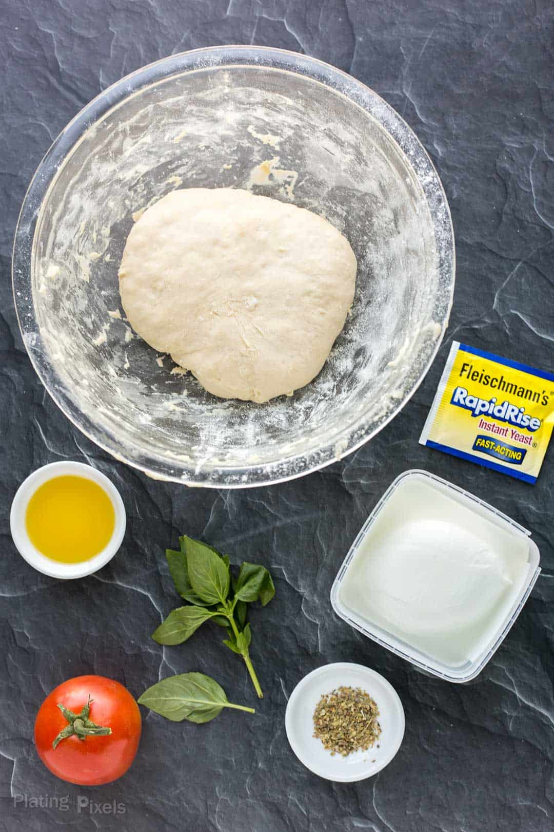 Ingredient for making Caprese pizza on a marble counter
