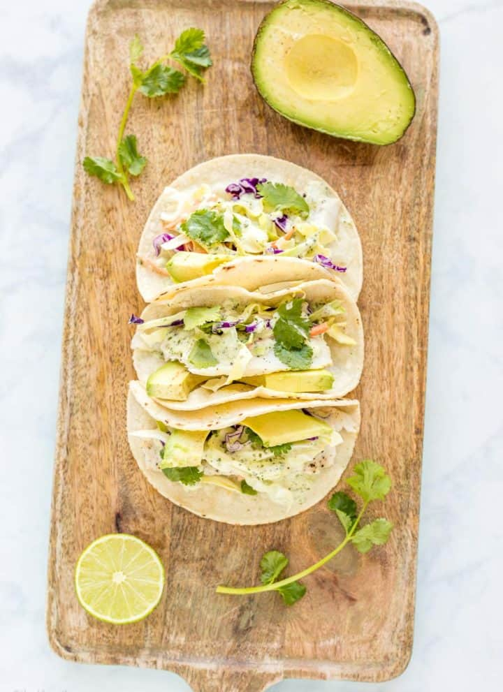 Three prepared Baked Fish Tacos with Cilantro Dressing on a serving platter