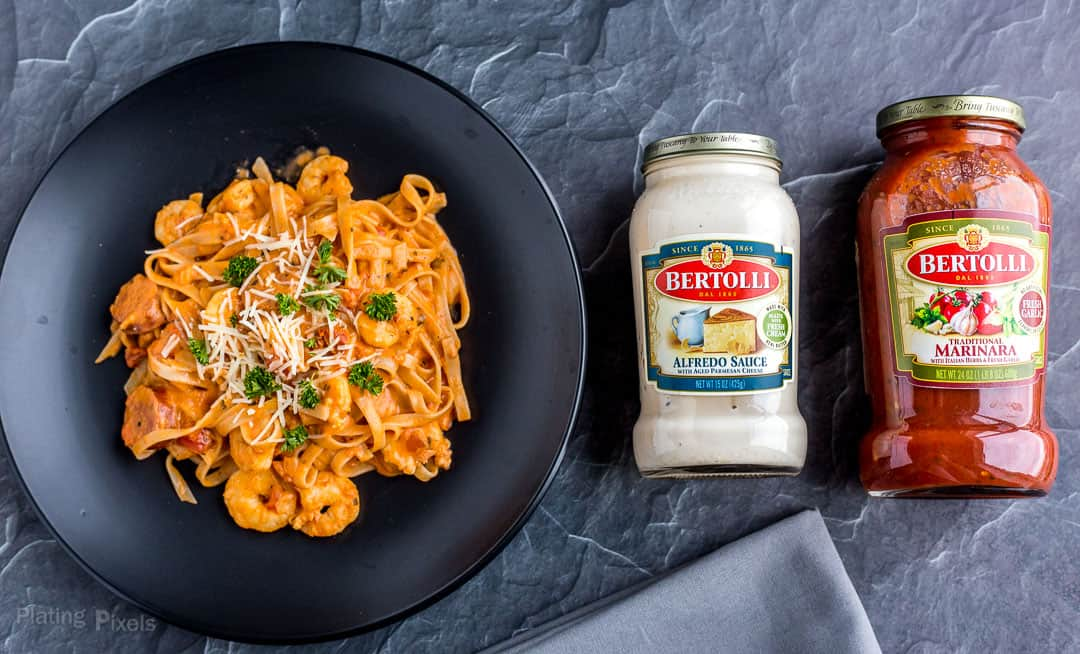 A plate of Shrimp and Sausage Spaghetti next to jars of Bertolli Sauces