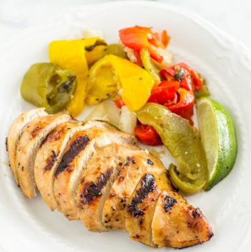 Sliced Grilled Chicken Fajitas on a plate next to the marinated vegetables
