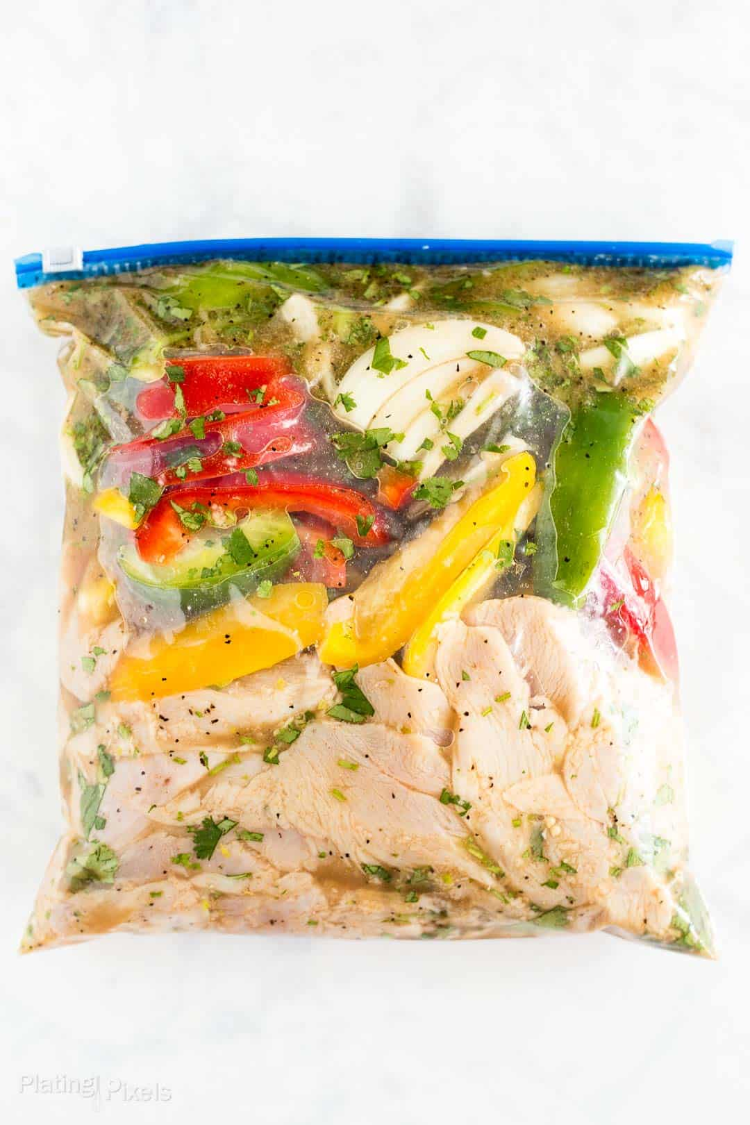 Process shot of chicken and vegetables marinating in a bag to make fajitas