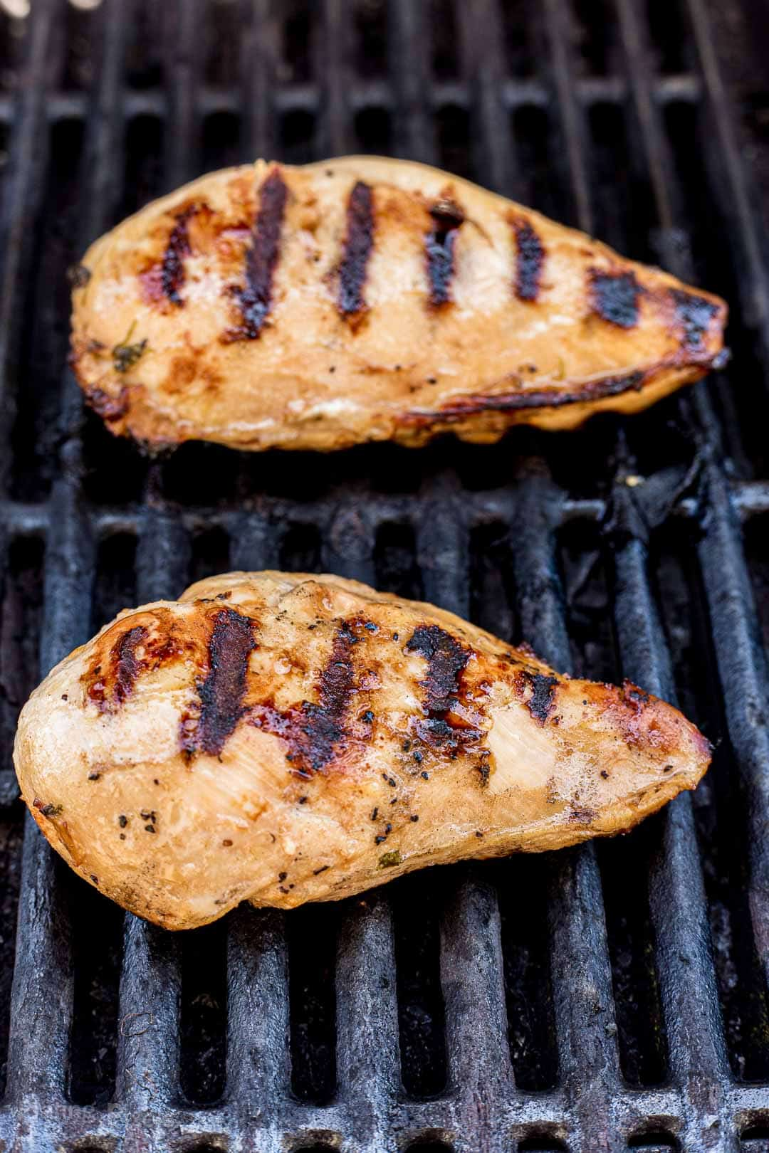 Process shot of grilling fajita marinated chicken breasts on a gas grill