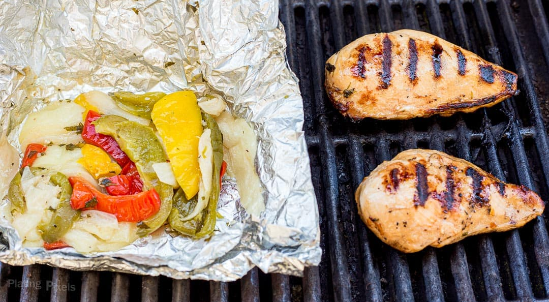 A pouch of fajita marinated vegetables cooking next to chicken breasts on a grill