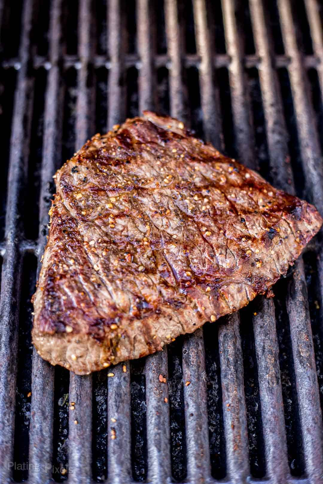 Process shot of a London Broil steak cooking on a gas grill