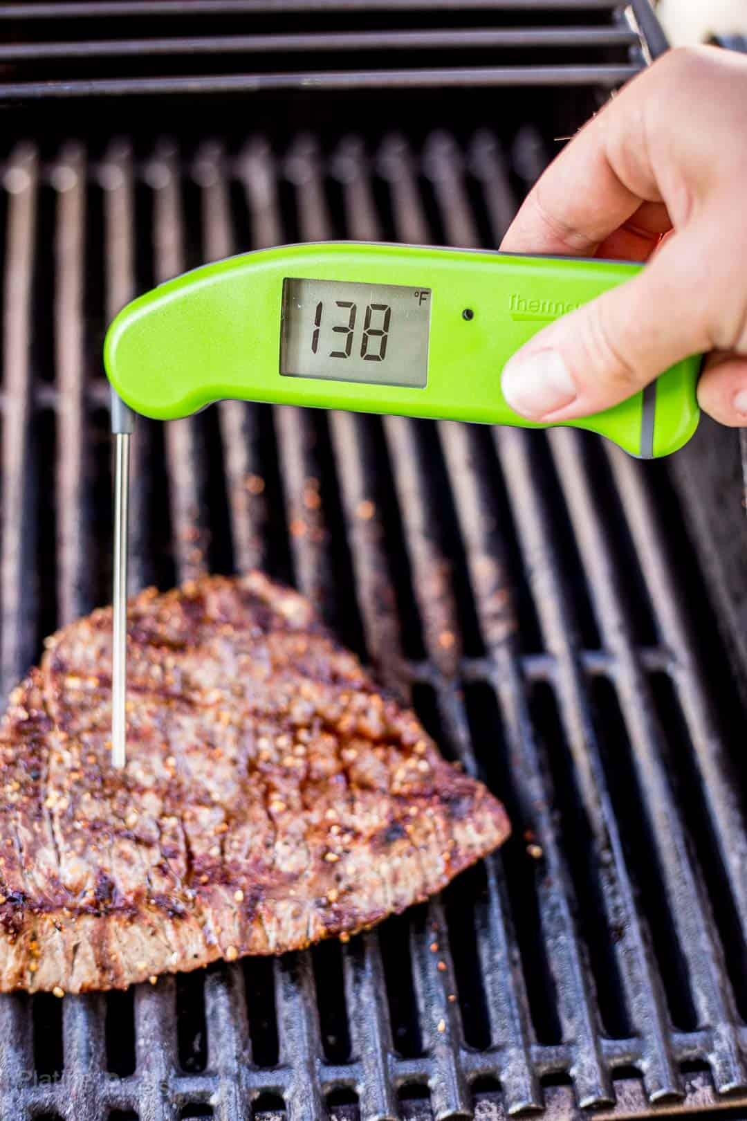 Checking the temperature of a London Broil on the grill with a digital thermometer