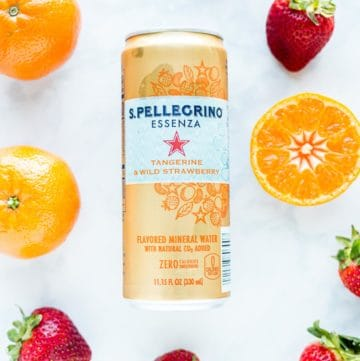 Can of S. Pellegrino next to fresh strawberries and tangerines
