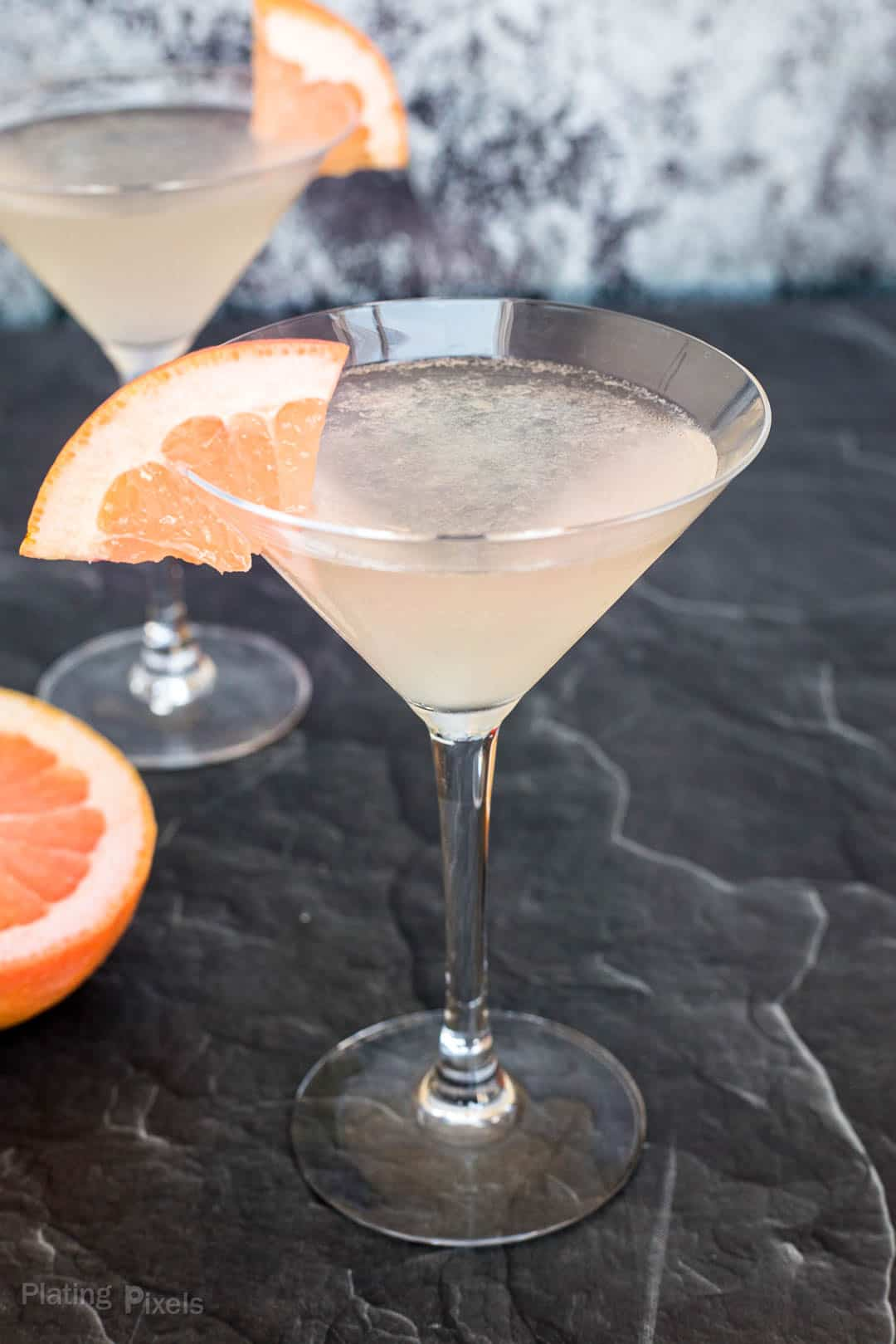 Close up a Grapefruit Martini on a black marble counter