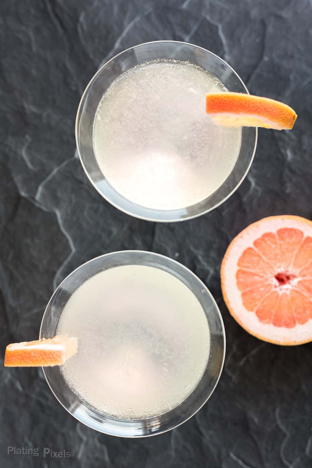 Overhead shot of two Grapefruit Martinis garnished with grapefruit wedges
