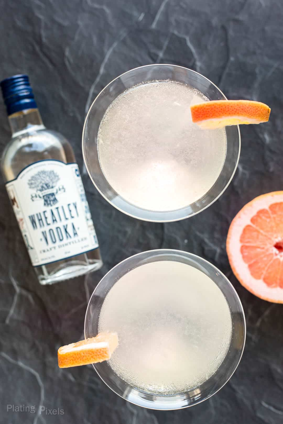 Overhead shot of Grapefruit Martinis next to a bottle of Wheatley Vodka