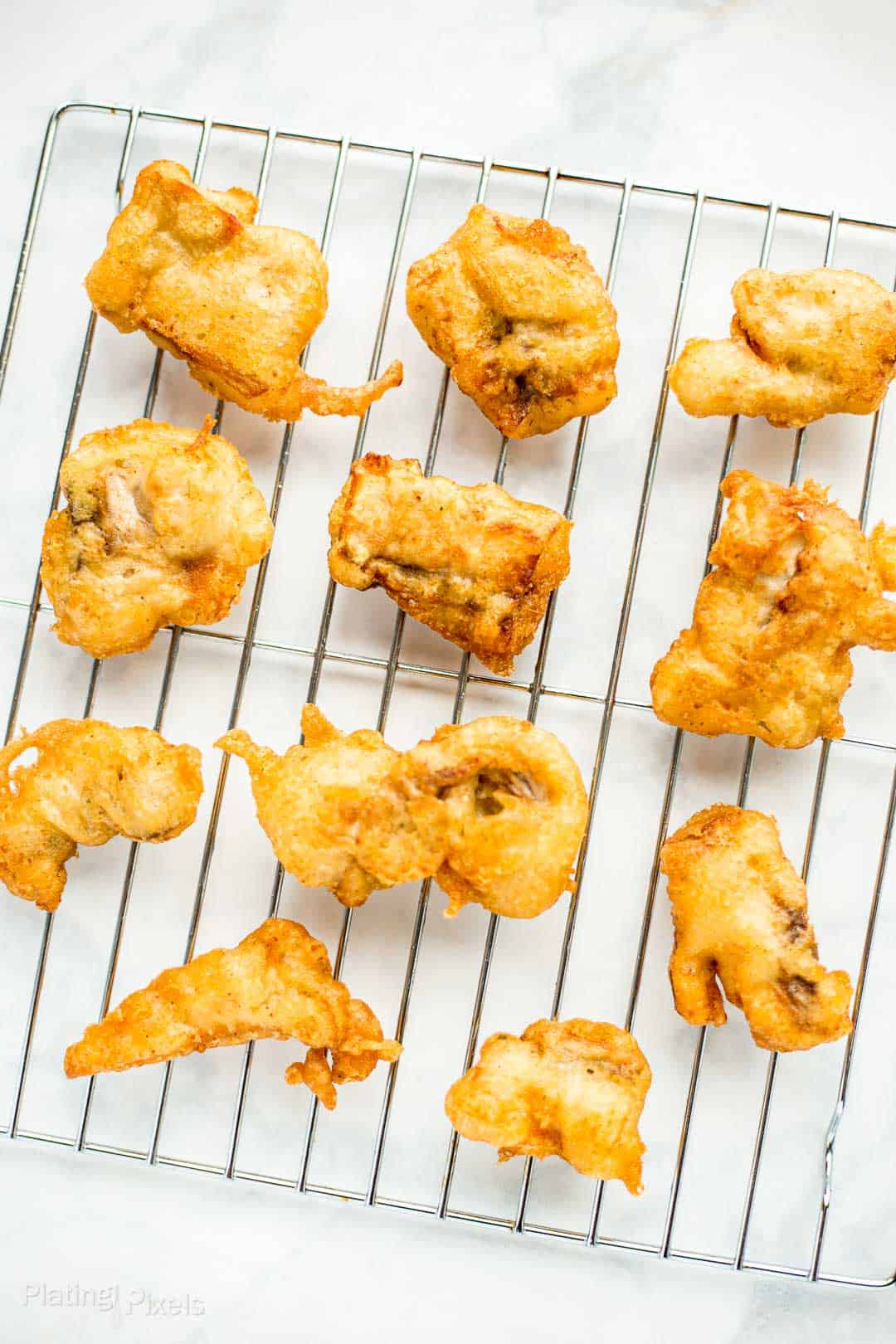 Golden Beer Battered Fried Fish pieces on a wire rack