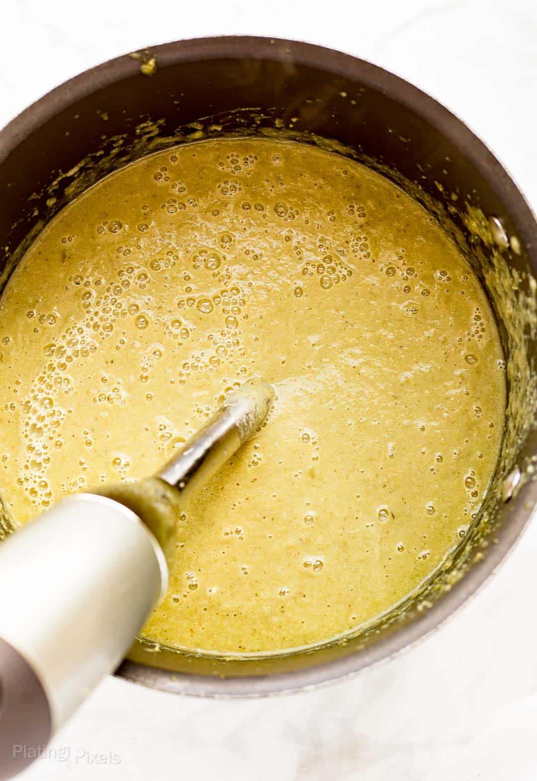 Process shot of blending leek soup with an immersion blender