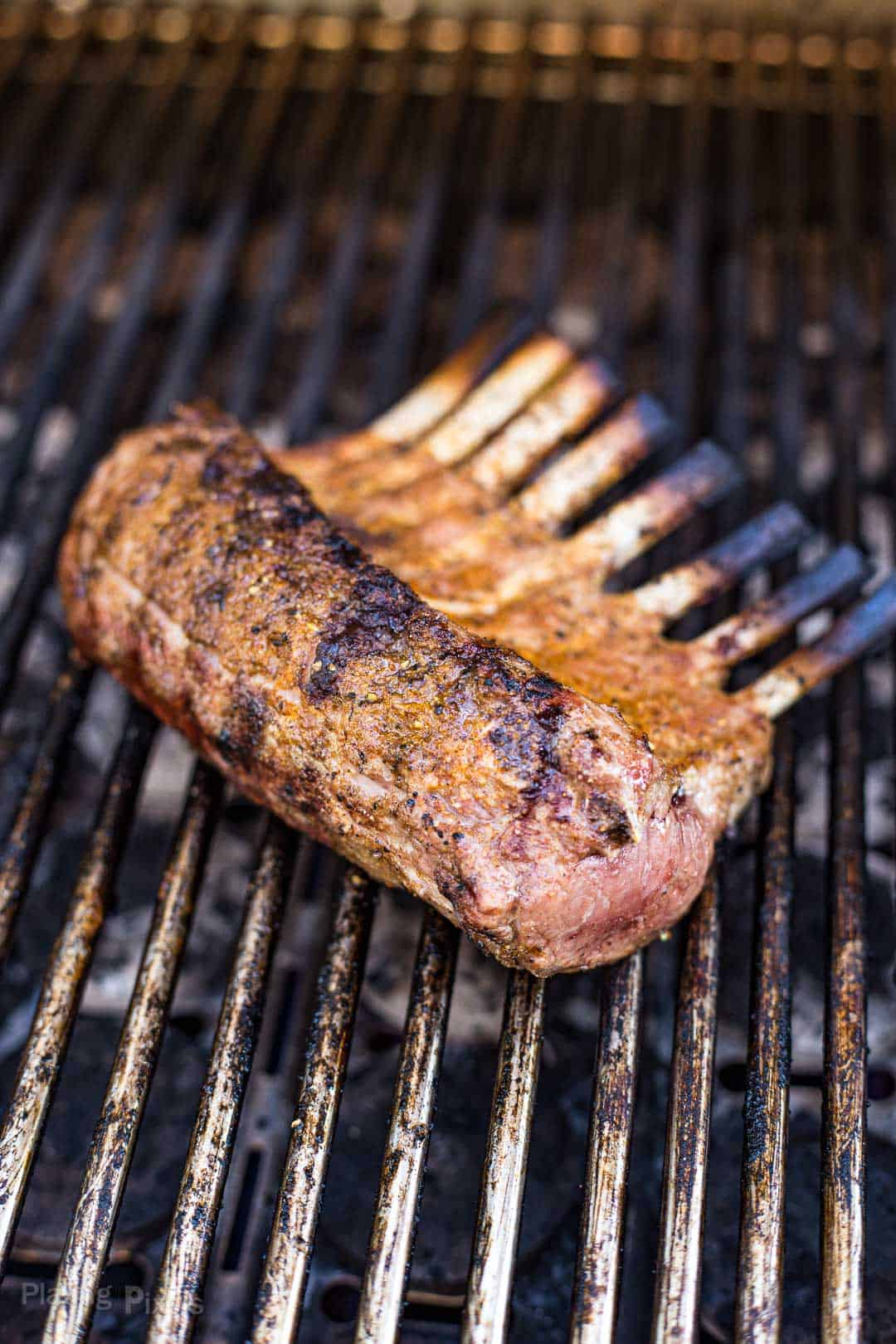 A rack of lamb cooking on a gas grill