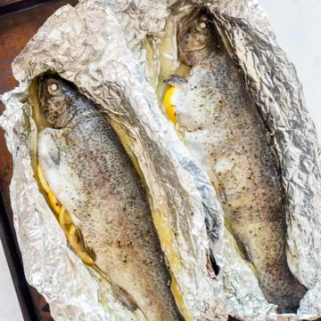 Two baked trouts on foil on a baking sheet