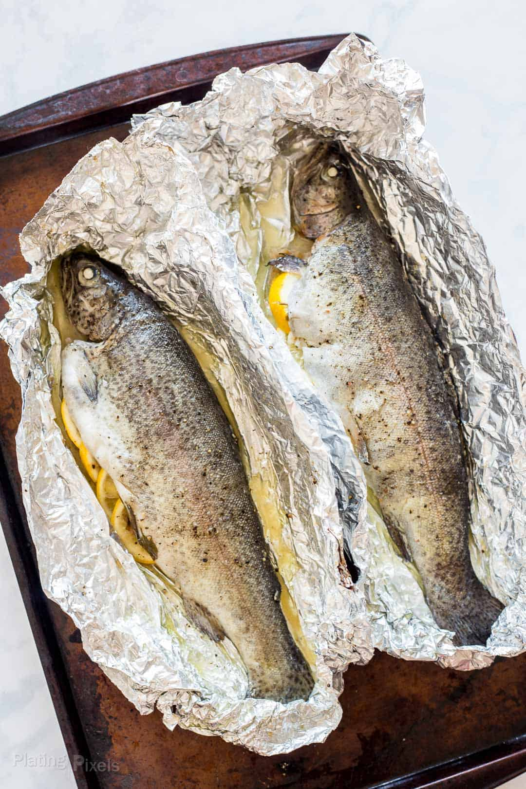 Two oven baked trouts on foil on a baking sheet