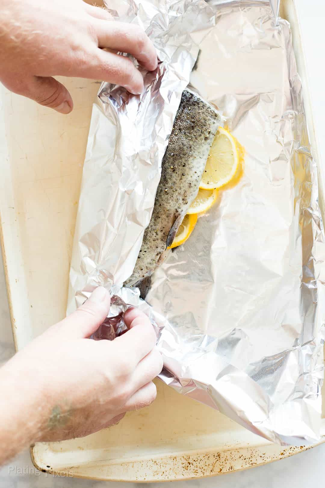 Process shot of sealing a whole trout in foil